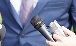 close-up of media professional with mic and recorder in hand
