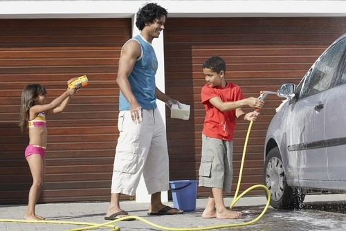 A father and his two children happily washing their car in the sun