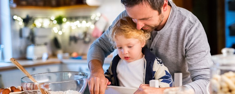 Father shows toddler how to use rolling pin in kitchen
