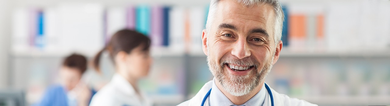 Doctor with white coat and stethoscope smiles at camera