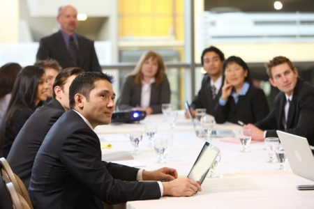suited professionals seated at a conference table image