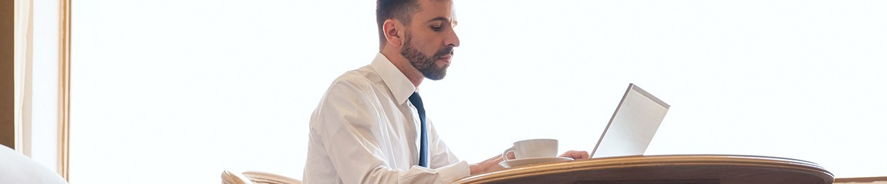 Man in shirt and tie pays invoice from laptop while drinking cup of coffee