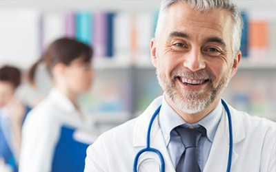 doctor in white coat with stethoscope smiles for camera