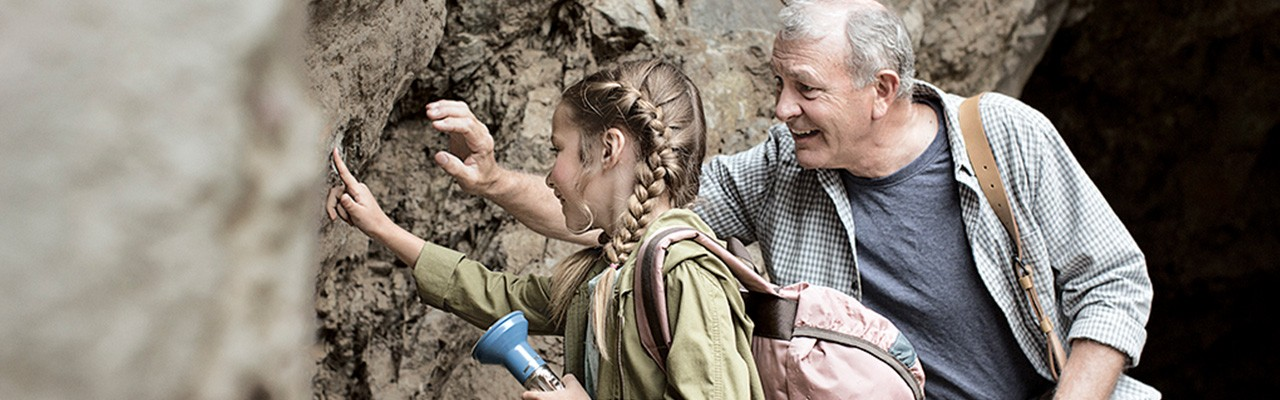 child explores rock formations with her grandfather