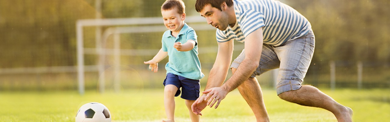 father plays soccer with his toddler son on soccer field