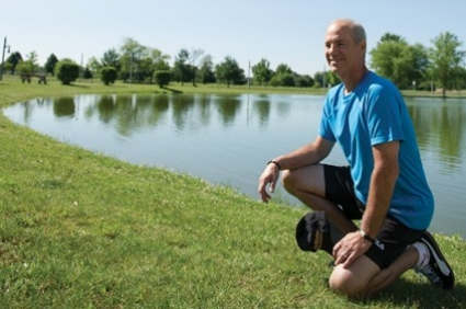 Mike esposito kneels for a picture on a grassy lawn in front of a pond