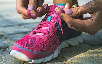 close up of runner lacing up pink running shoes