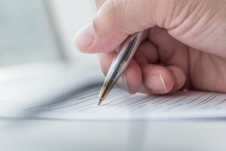 Close up of person filling out a form