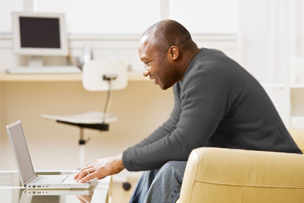 Male patient reads cultural resources on laptop